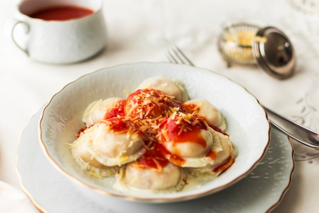 Ravioli stuffed with cheese and tomato sauce in the bowl Free Photo