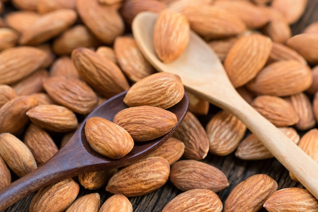 Raw almonds nut on wood spoon and wooden table. Premium Photo