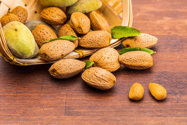 Raw almonds, peeled, with peel, skin (almendrucos) and almond leaves. Premium Photo