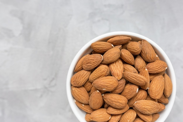 Raw almonds in a porcelain bowl on gray Premium Photo