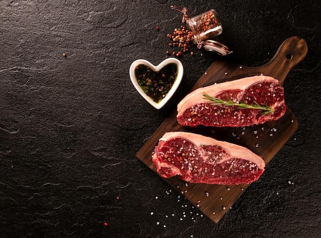 어두운 커팅 보드에 요리하기위한 원시 멸치 고기. 나무 배경입니다. 프리미엄 사진