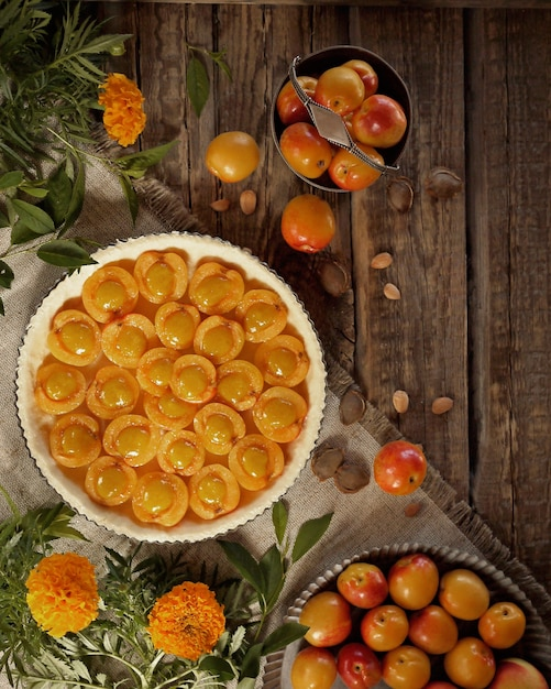 Raw apricot pie before baking. apricots and marigolds on wooden table. top view Premium Photo