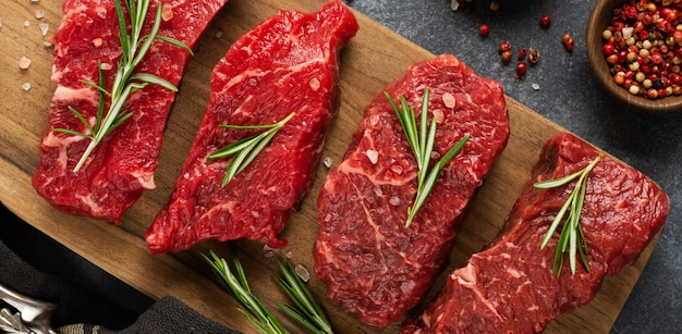 Raw beef steak with spices, onions and rosemary on dark slate or concrete background. top view Premium Photo