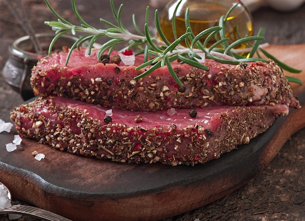 Raw beef steak with spices and a sprig of rosemary Free Photo