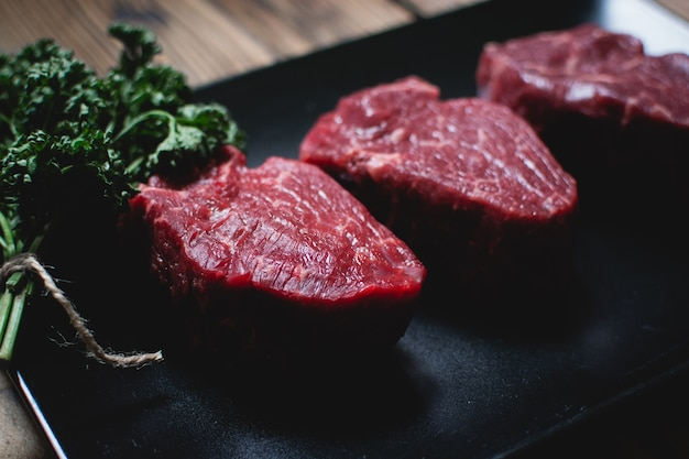 Raw beef steaks on a black plate Free Photo