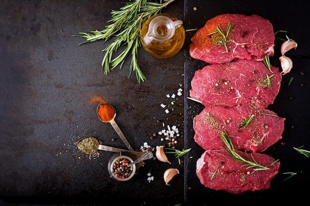 Сырые говяжьи стейки со специями и розмарином. плоская планировка. вид сверху Бесплатные Фотографии