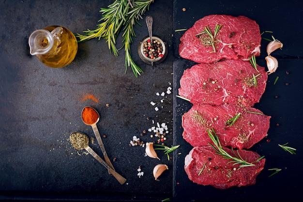 향신료와 로즈마리와 원시 쇠고기 스테이크입니다. 평평하다. 평면도 무료 사진