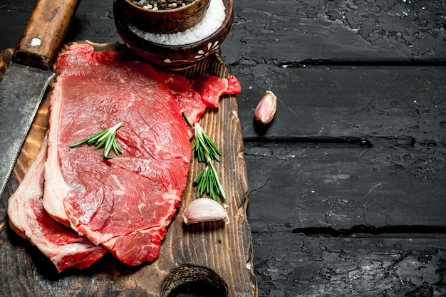 Raw beef steaks with spices and salt on dark rustic table. Premium Photo