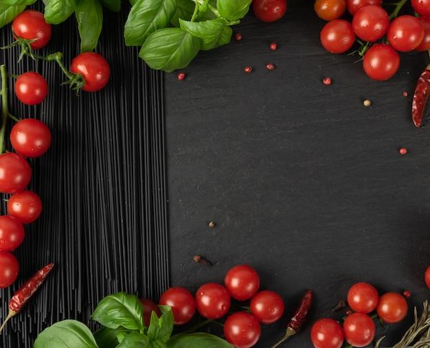 Raw black homemade spaghetti on dark background. dry black noodles texture Premium Photo