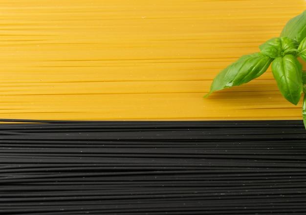 어두운 배경에 원시 검은 수 제 스파게티. 건조 검정색과 노란색 계란 국수 텍스처 프리미엄 사진