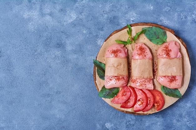 Сырое мясо грудки со специями на деревянной доске на синем Бесплатные Фотографии