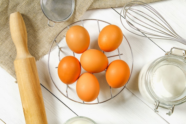 Raw brown chicken eggs, milk, sugar, flour, whisk, rolling pin Premium Photo