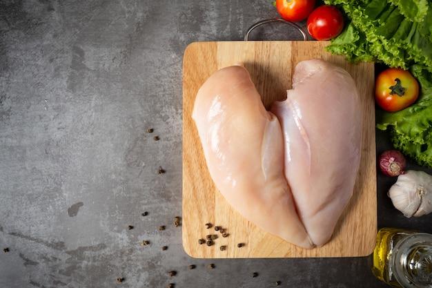 木製のまな板に生の鶏の胸肉。 無料写真