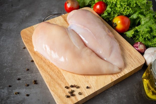 Raw chicken breasts on wooden cutting board. Free Photo