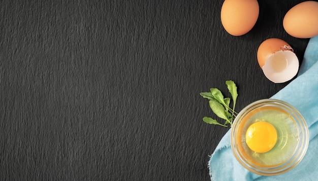 卵殻の隣のガラスカップに生の鶏卵 無料写真