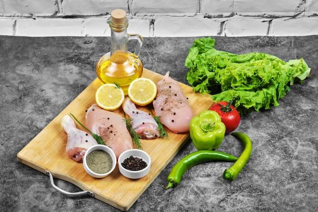 Сырое куриное филе и ножки на деревянной тарелке со свежими овощами, специями и стаканом масла. Бесплатные Фотографии