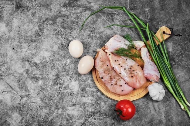 원시 치킨 필렛 그리고 신선한 야채와 함께 나무 접시에 다리. 무료 사진