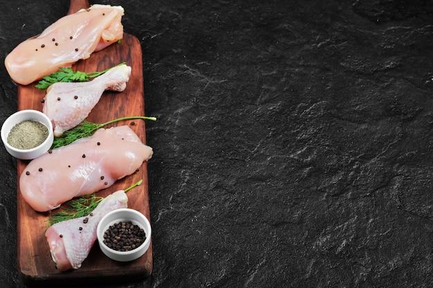 Filetto di pollo crudo e gambe sul piatto di legno Foto Gratuite