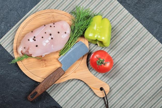 Сырое куриное филе на деревянной доске с болгарским перцем, ножом и помидорами. Бесплатные Фотографии
