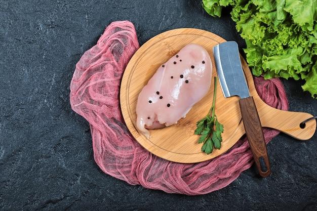 Сырое куриное филе на деревянной доске с зеленью и ножом. Бесплатные Фотографии