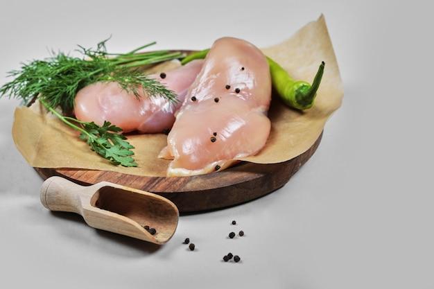 숟가락으로 나무 접시에 원시 치킨 필렛 무료 사진