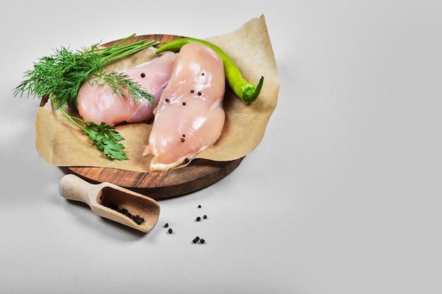 Сырое куриное филе на деревянной тарелке с ложкой Бесплатные Фотографии