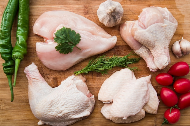 Raw chicken and ingredients for cooking on wooden table Free Photo