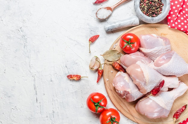 Raw chicken legs on cutting board with spices and herbs. Premium Photo