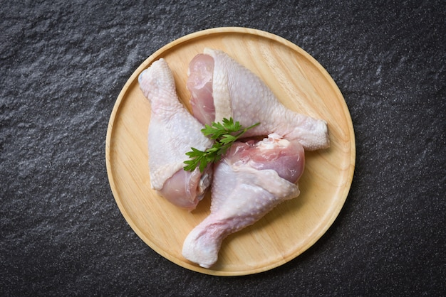 Raw chicken legs with herbs on wooden plate Premium Photo
