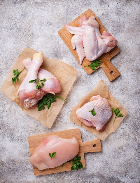 Raw chicken meat fillet, thigh, wings and legs Premium Photo