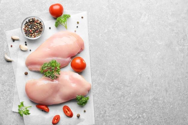 회색 배경에 향신료와 원시 닭고기 프리미엄 사진