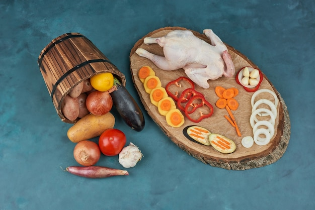 バケツにハーブと野菜を入れた木の板に生の鶏肉。 無料写真