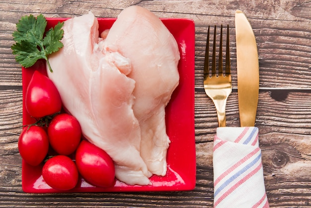 Raw chicken and tomatoes in plate with fork and knife Free Photo