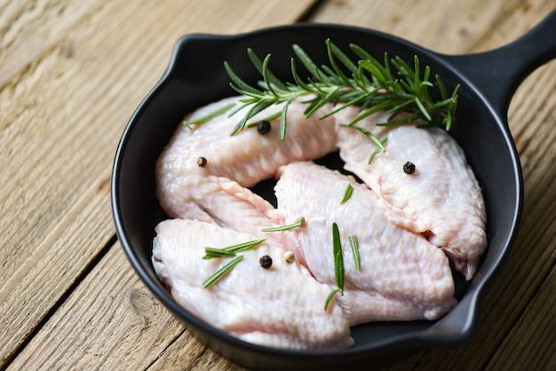Сырые куриные крылышки, зелень и специи для приготовления тайской азиатской еды курица с розмарином Premium Фотографии