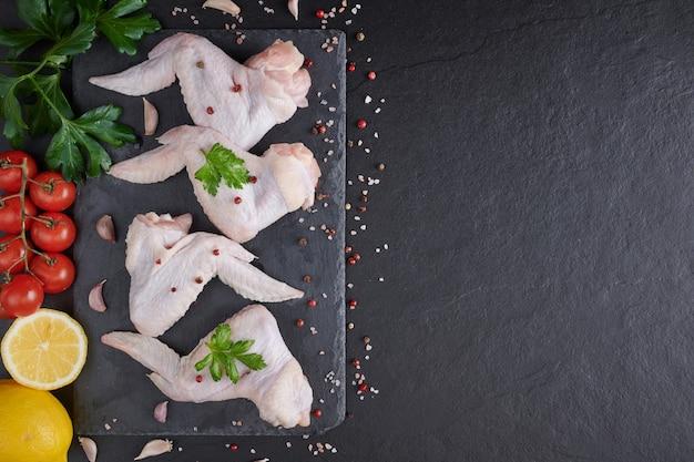 요리 재료와 생 닭 날개. 생고기. 닭 날개는 검은 배경에 야채와 향신료와 함께 나무 보드에 거짓말. 무료 사진