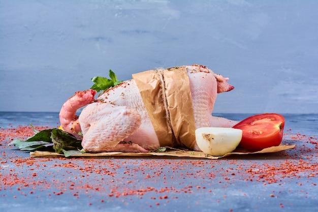 Сырая курица с зеленью на деревянной доске на синем Бесплатные Фотографии