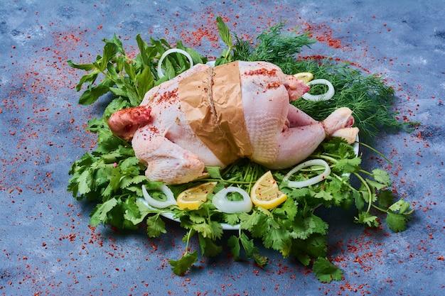 Pollo crudo con erbe su una tavola di legno sull'azzurro Foto Gratuite