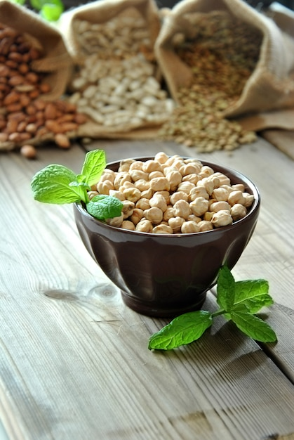 Raw chickpeas in a brown bowl with herbs Premium Photo