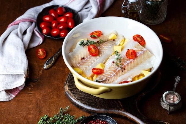 Сырое филе трески с картофелем и помидорами в керамической форме для запекания Premium Фотографии