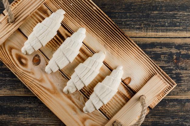 Сырцовый круассан в деревенском подносе на деревянном столе. плоская планировка Бесплатные Фотографии