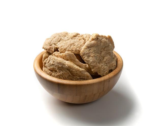 Сырое обезвоженное соевое мясо или куски сои в деревянной изолированной миске. текстурированный растительный белок, также известный как текстурированный соевый белок или tsp Premium Фотографии