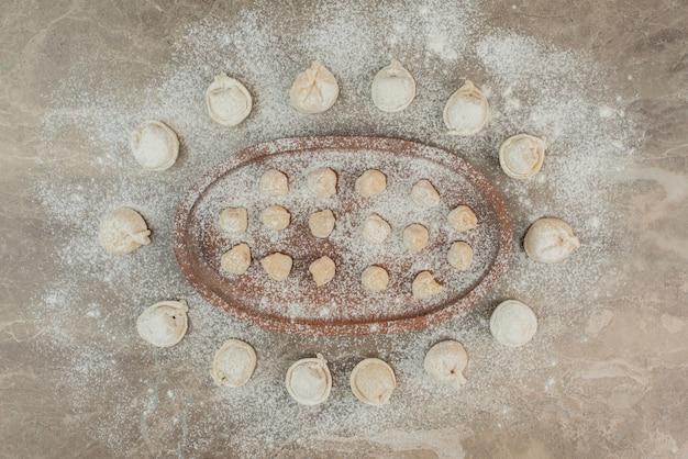 小麦粉と木の板の生餃子。 無料写真