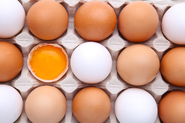 Raw eggs in carton for background. chicken egg is half broken among other eggs Premium Photo