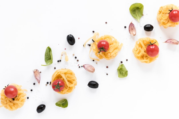 Raw fettuccine pasta; cherry tomato; black olive; garlic clove and basil leaves isolated over white background Free Photo