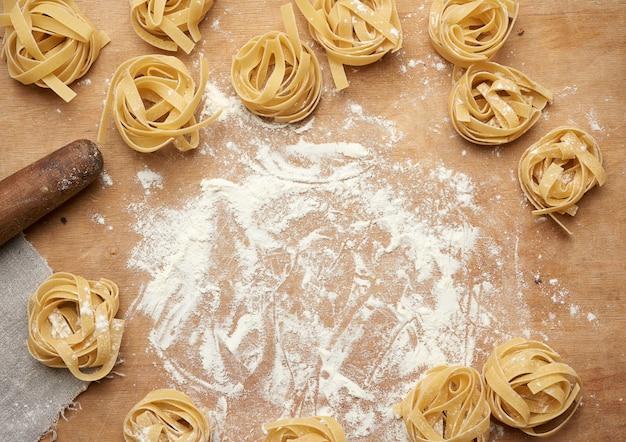 白い小麦粉と茶色の木の板に生のフェットチーネパスタ Premium写真