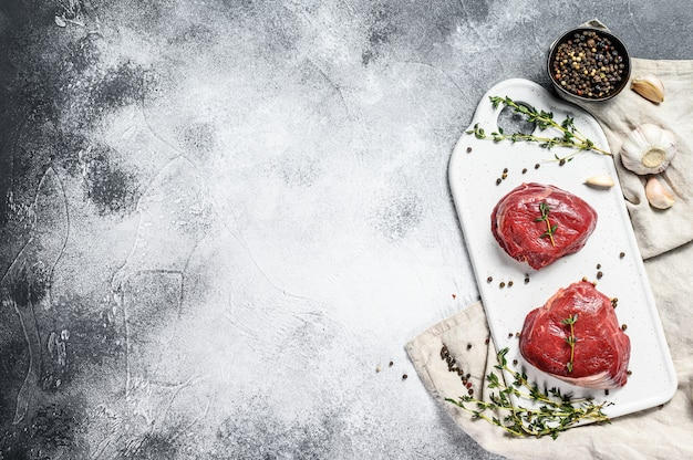 Raw filet mignon steak on a white chopping board. beef tenderloin. gray background. top view. space for text Premium Photo
