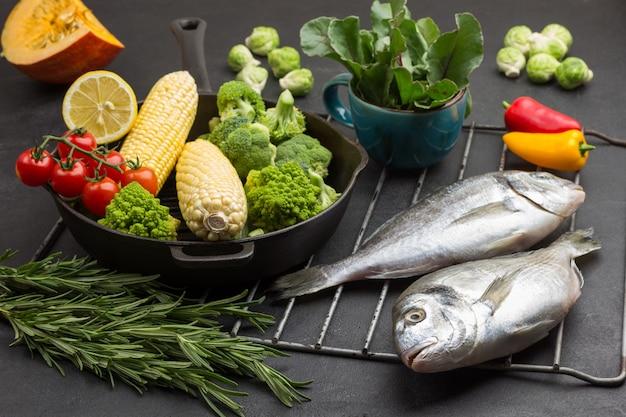 生の魚と野菜のグリルでフライパン。緑の葉とマグカップ。 Premium写真