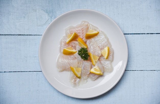 Raw fish fillet piece with lemon on white plate Premium Photo