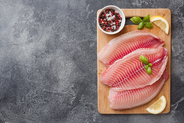 Raw fish fillet of tilapia on a cutting board with lemon and spices. dark table with copy space. Premium Photo