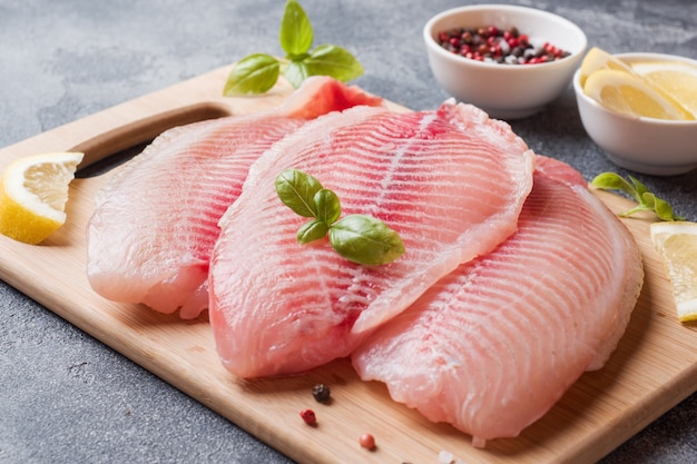 Raw fish fillet of tilapia on a cutting board with lemon and spices. dark table Premium Photo